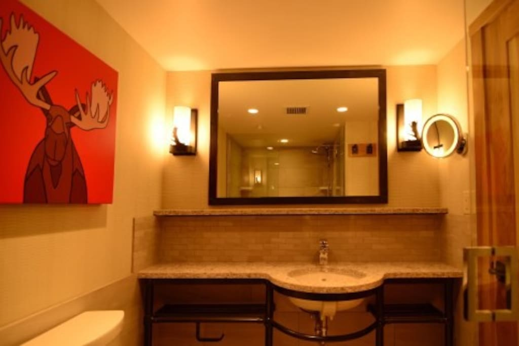 The spacious bathroom features granite countertops and beautiful touches.