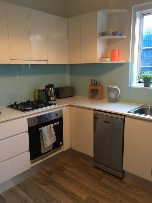 Renovated kitchen with small juliet balcony, washing machine, dishwasher and gas stove.