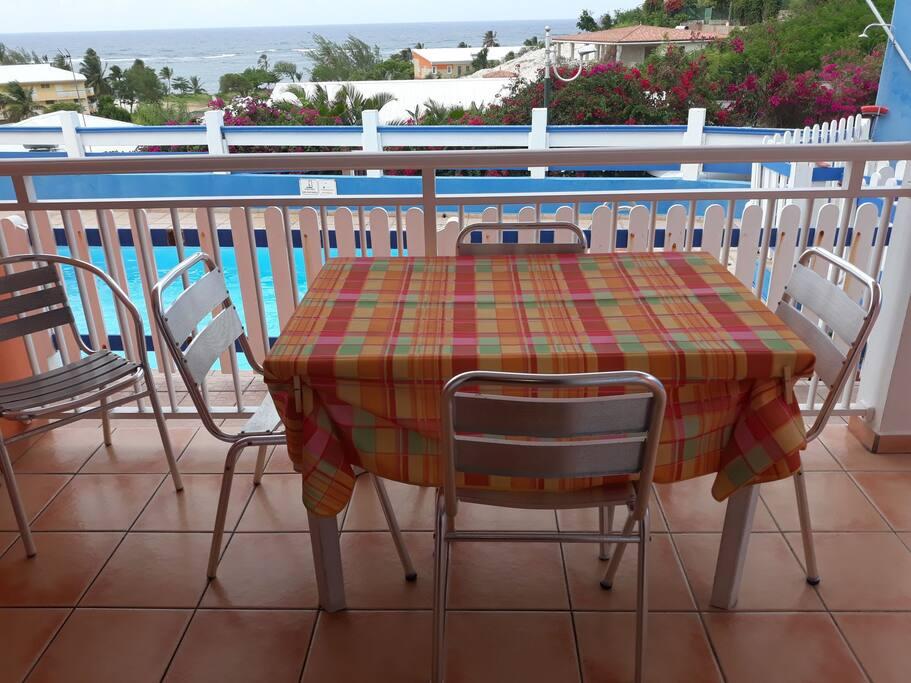 Terrasse face à la piscine et à la mer