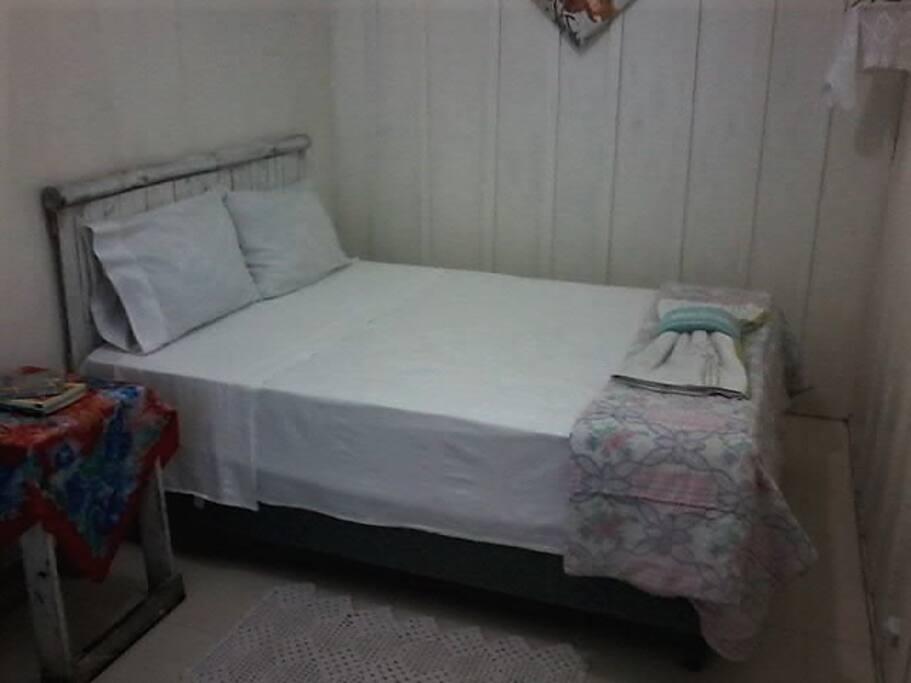 Quarto com cama de casal, roupa de cama e toalhas limpinhas
