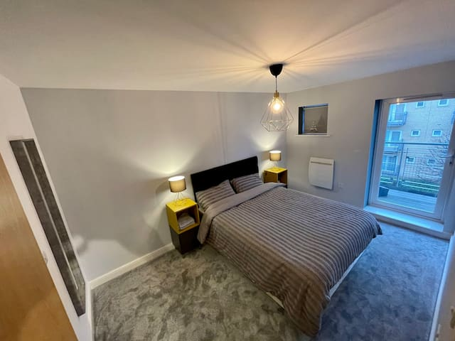 King size bed in master bedroom with view out to one of the private balconies over looking the river