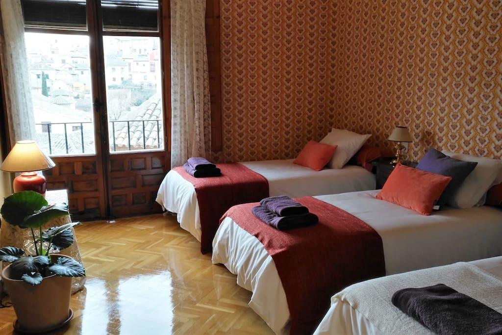 Habitacion Naranja con balcón con vistas. 3 camas individuales y armario emprotrado
