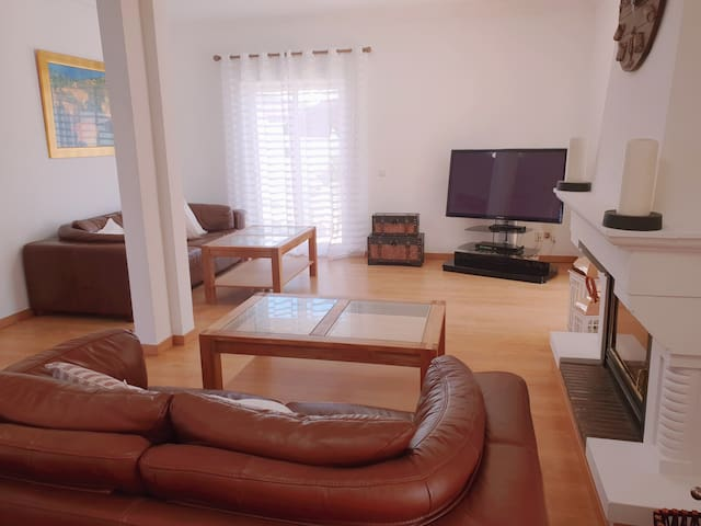 Large living room with traditional fireplace. Flat screen tv with satellite channels and DVD player.  Patio doors leading to garden and pool area.