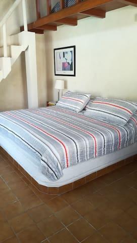Recámara número 2, con una cama king size. Al fondo está la escalera que conduce a un tapanco en el que hay 5 camas individuales. Aire acondicionado en la habitación.