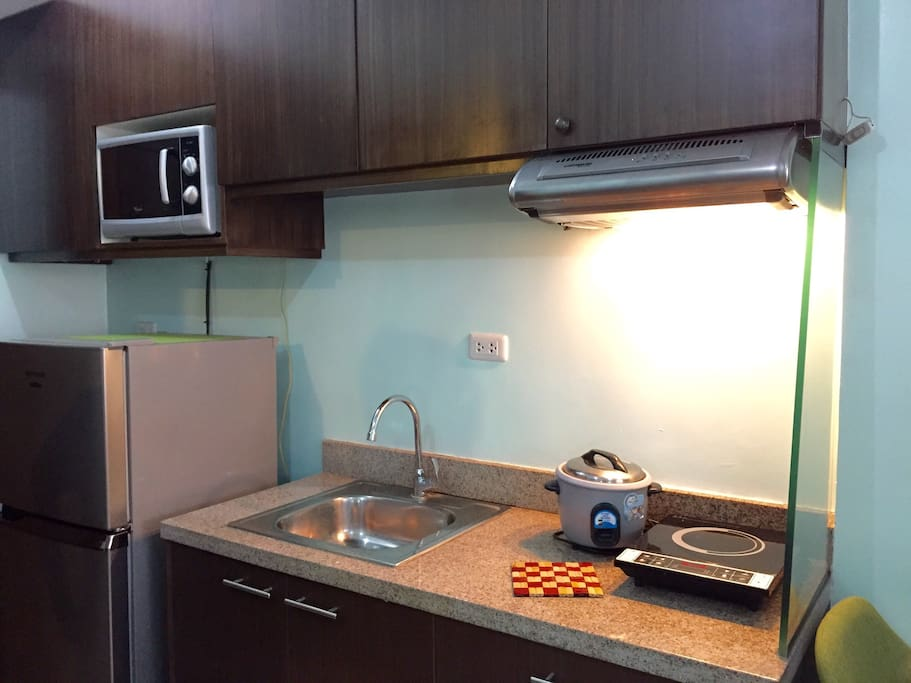 Fully functional kitchen with microwave, refrigerator, rice cooker and induction stove. One gallon of water in the water dispenser is complimentary.