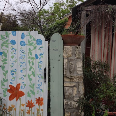 Enter the metal gate painted with flowers (just next to the carport). This is on W31st.