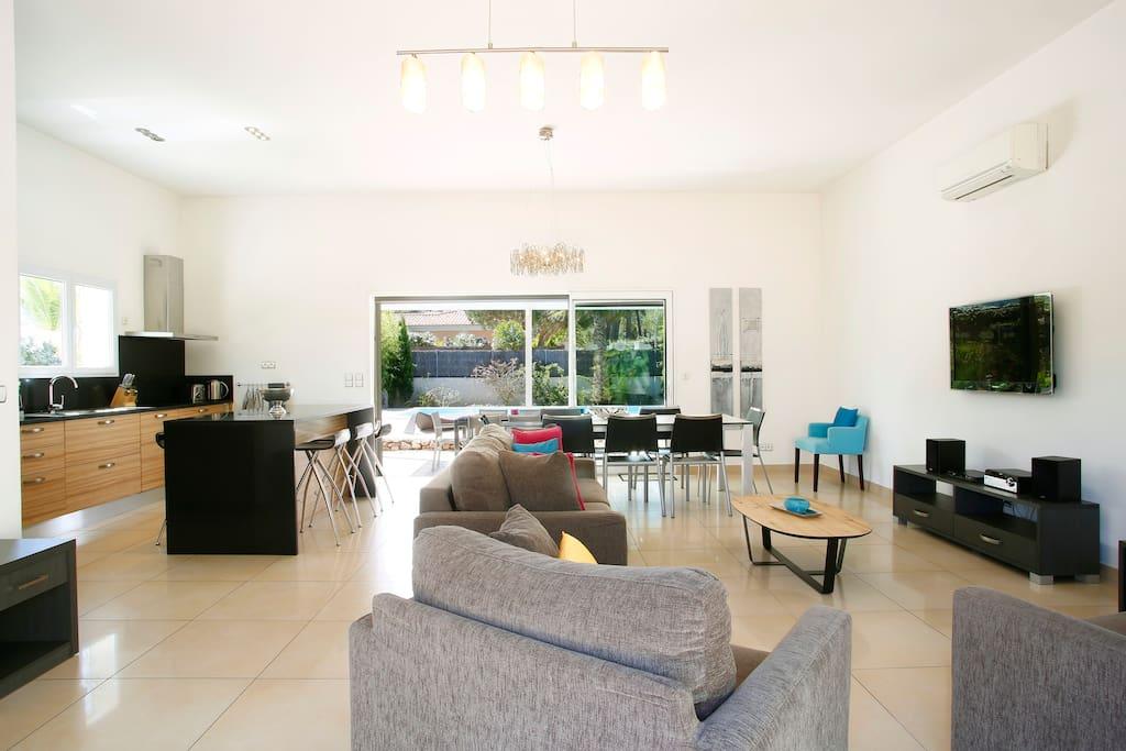 Un espace salon-salle à manger et cuisine convivial ouvrant sur deux terrasses