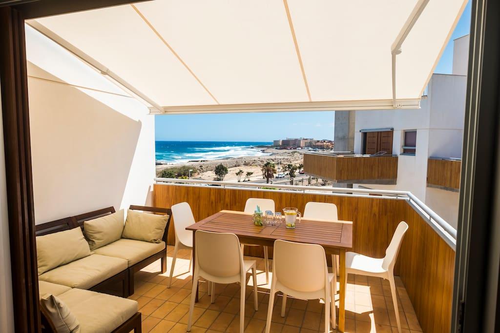 Die Terrasse mit automatischer Markise, die Schatten spendet, wenn es mal zu heiß ist in der Sonne. / The terrace with automatic sun-blind for the case that it is too warm in the sun.