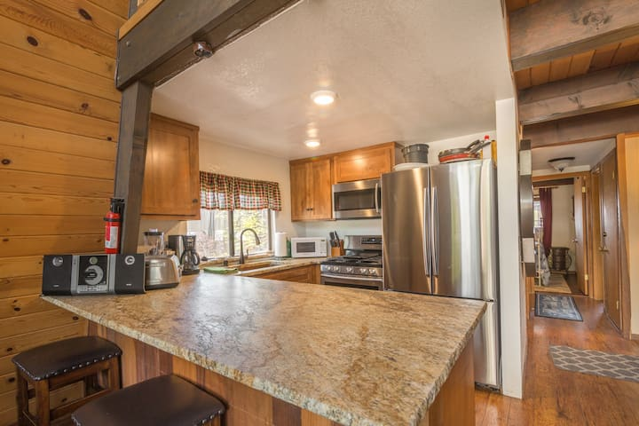 Additional seating at the large rustic slab granite kitchen counter.
