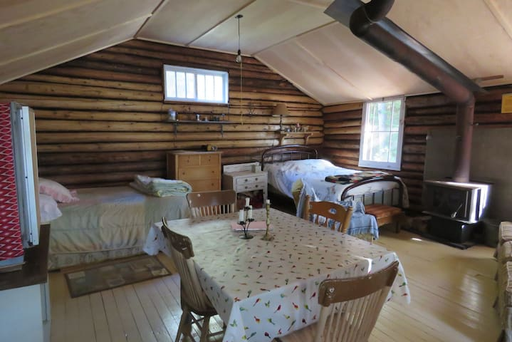 Inside main cabin: 2 beds (double and queen, bring sheets or sleeping bag), wood stove, dining table, sofa, solar-powered lighting