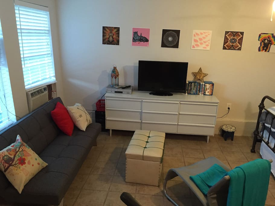 Cozy living area with chair, futon sofa (can fold down to sleep one), antenna tv, DVD/VCR player (with lots to watch).