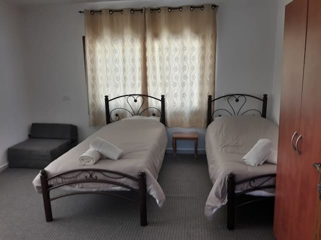 a room with two single beds + a sofa bed