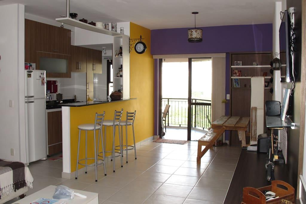 Sala ampla, cozinha americana. Sofá espaçoso e decoração alegre.