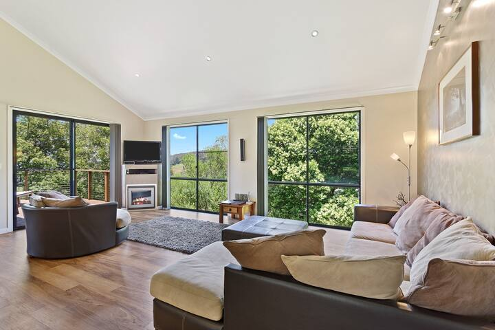Large airy lounge area with ambient fireplace and large TV. Views to the garden, veranda and national park