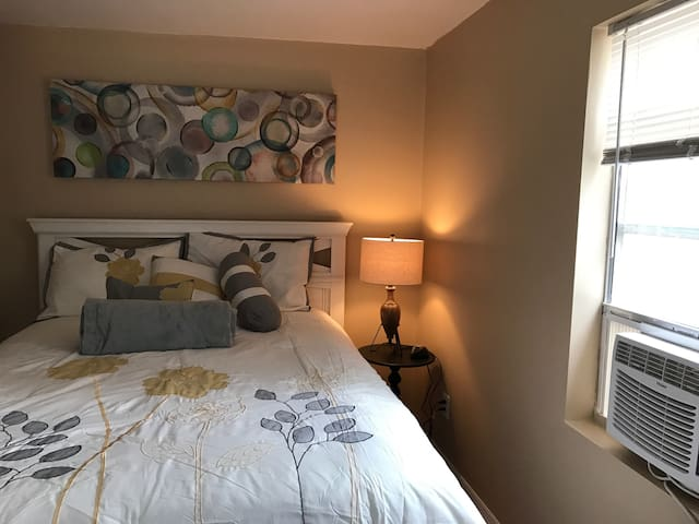 Larger bedroom with new wardrobe closet and air conditioner.
