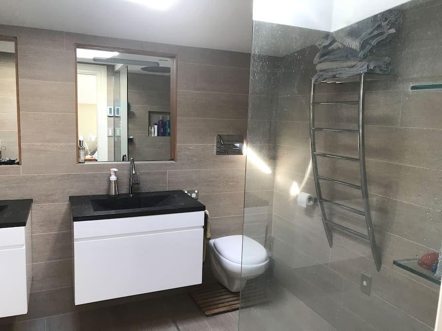 Upstairs ensuite bathroom.  Has a washing machine in the corner!  His and her sinks, rain shower as well as Methven Satin Jet shower head.