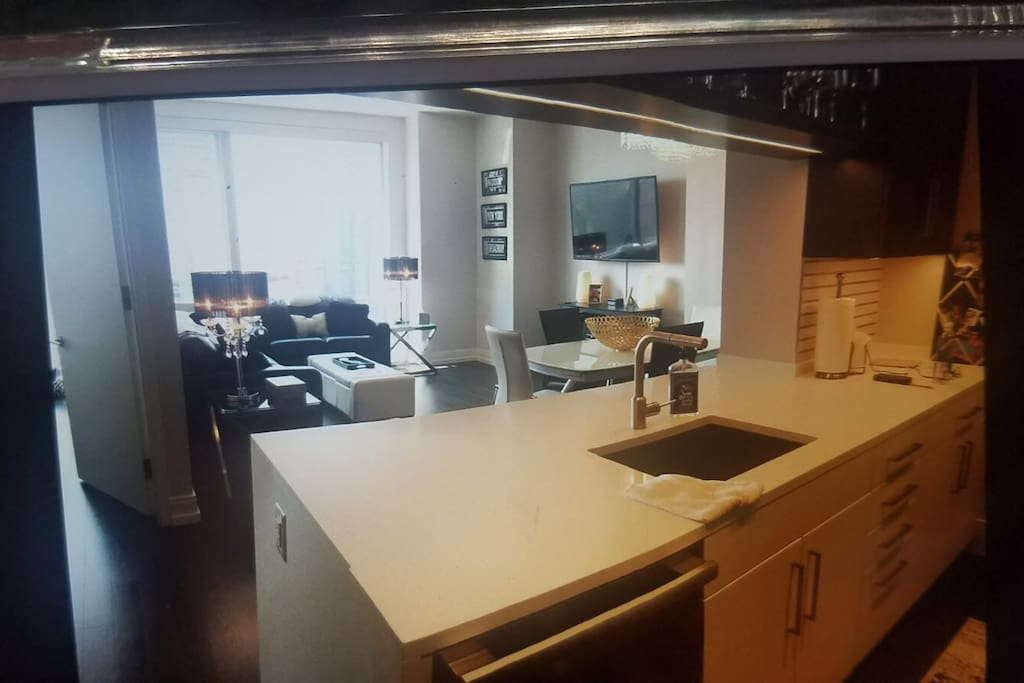 Kitchen counter has 3 stools and dining table that seats 6