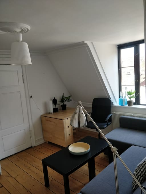 The second room have a large sofa, an extendable table, a cabinet, shelfs and coat hangers.