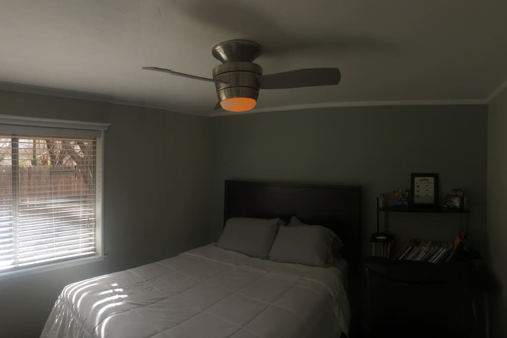 Guest bedroom with remote control fan and desk with oversize and extra comfy chair!