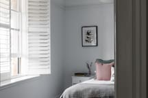Queen bedroom with beautiful plantation shutter blinds in every bedroom for privacy at Raffah House Accommodation Oatlands Tasmania