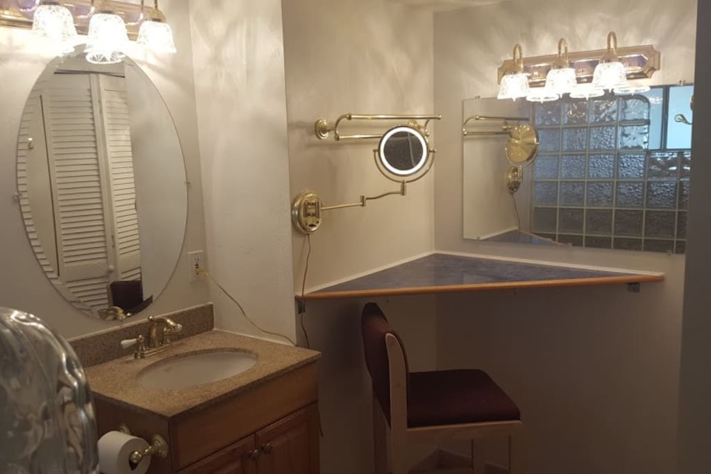 Bathroom vanity, make-up table, and lighted magnifying mirror looking from shower.