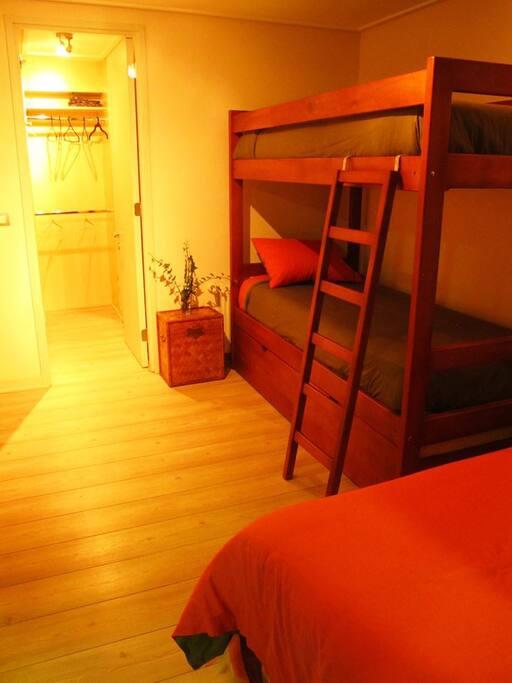 Segundo dormitorio con tres camas y baño en suite.