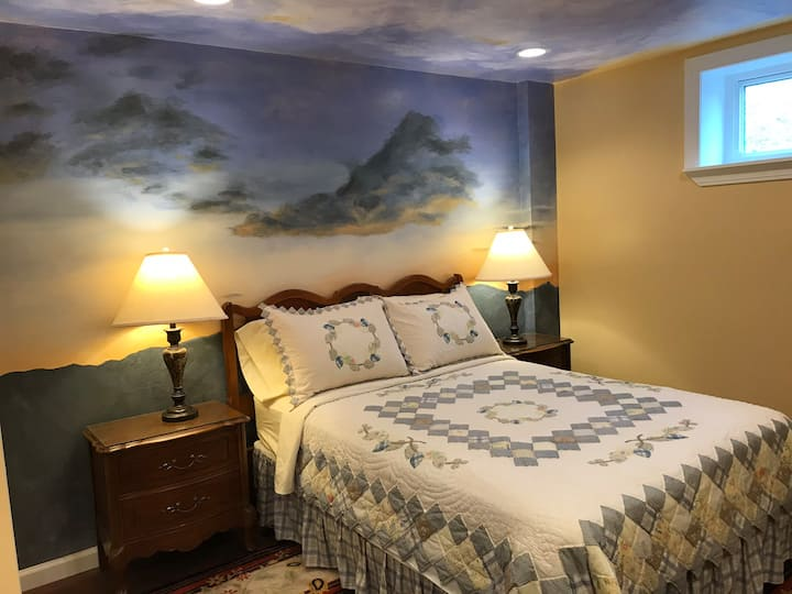 Cozy mural painted bedroom apartment.
