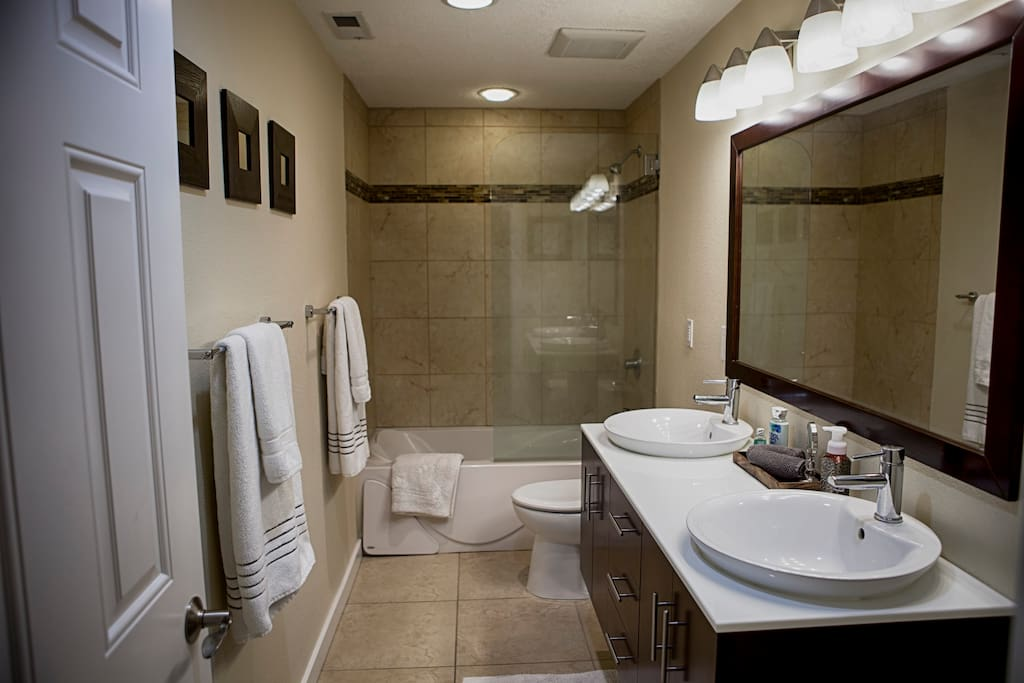 Private guest bath with dual vanity, shower, and a jetted tub.