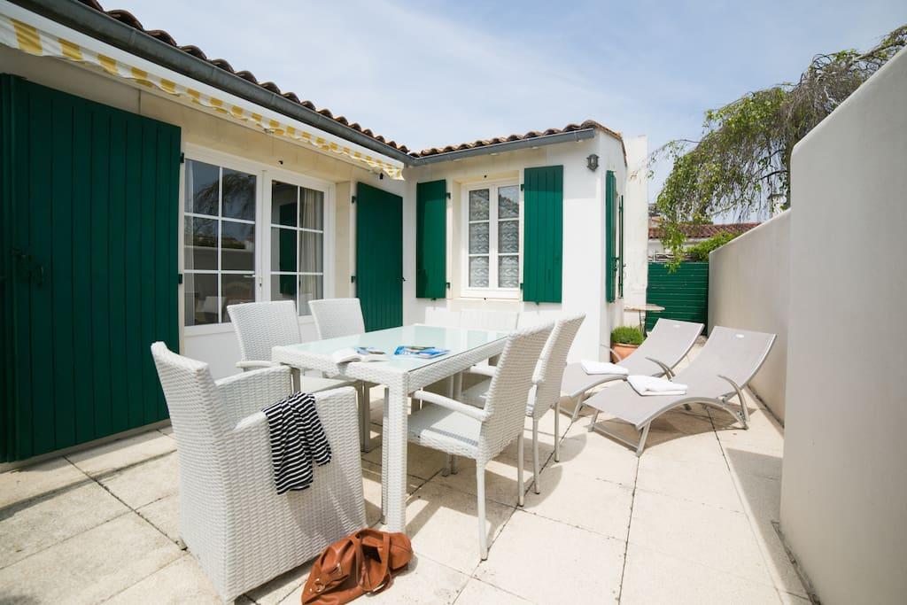 Terrasse privative avec salon de jardin et bains de soleil