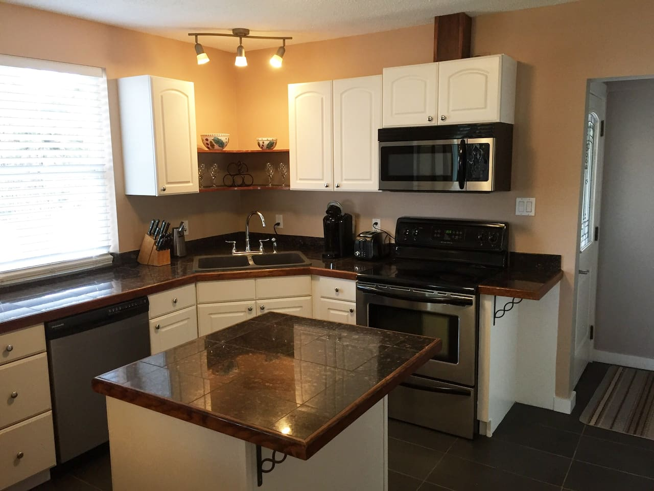 Kitchen with full amenities including keurig coffee maker, dishwasher, full sized stove, fridge, microwave oven, dishware and cookware.