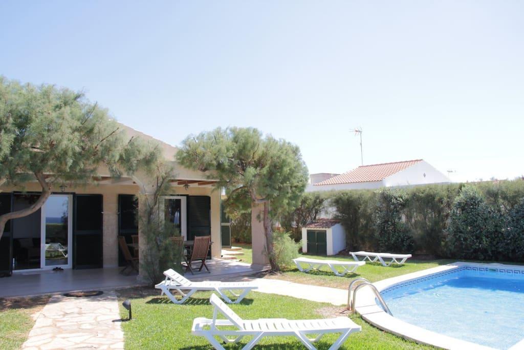 Fachada de la villa, terraza y piscina con mobiliario exterior