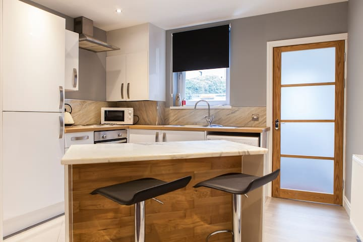 Open plan kitchen area with solid marble breakfast bar
