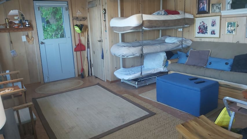 Main cabin features futon double bed and three fun bunk beds, salvaged from a naval minesweeper. There is a walk-in closet/changing room.