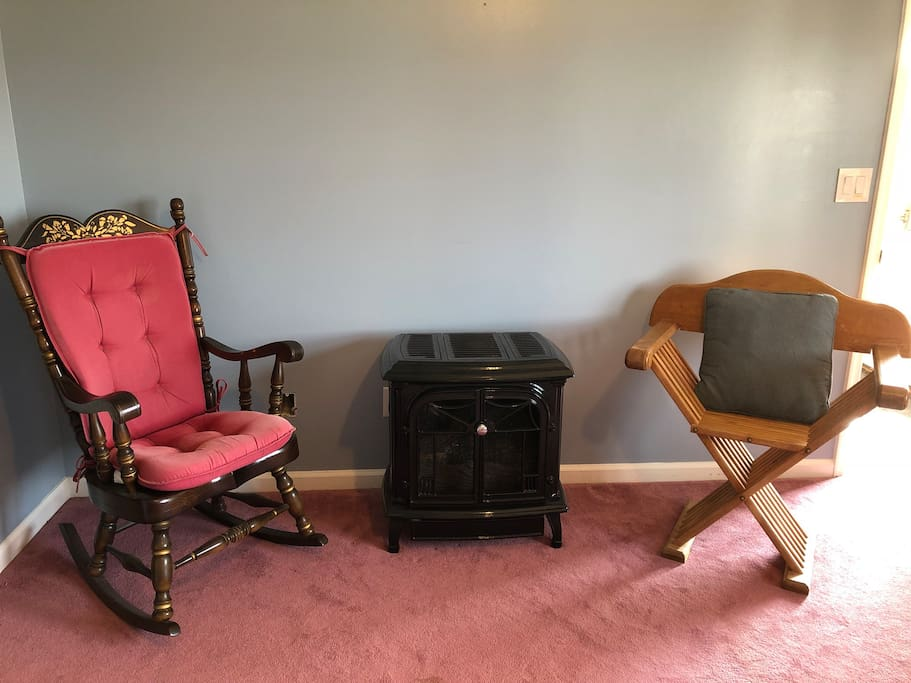 A comfortable sitting area by the fireplace in the room.