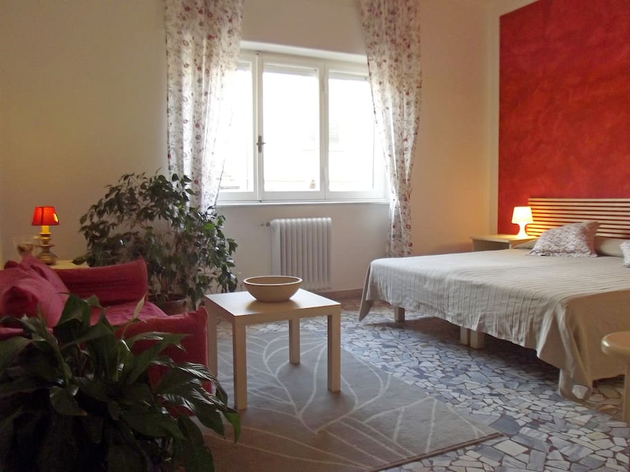 The red room with a double bed and living space