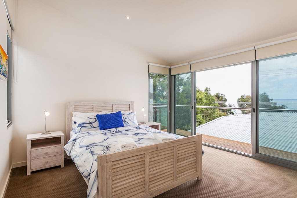 Master bedroom with private deck & ocean views.  Upstairs
