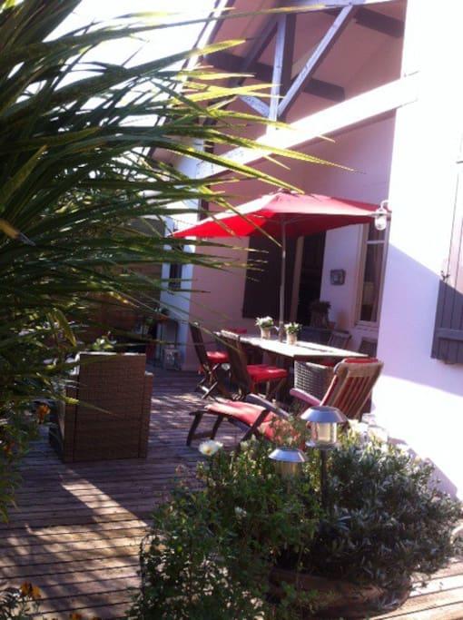 Coin repas sur terrasse avant fleurie et salon de jardin
