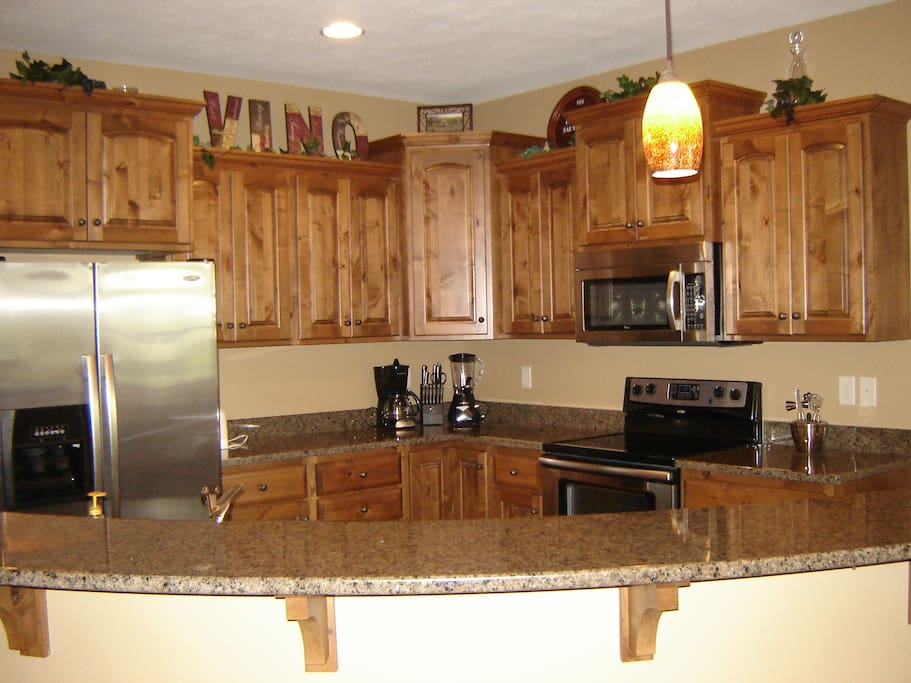 Large kitchen with granite counters and stainless steel appliances.