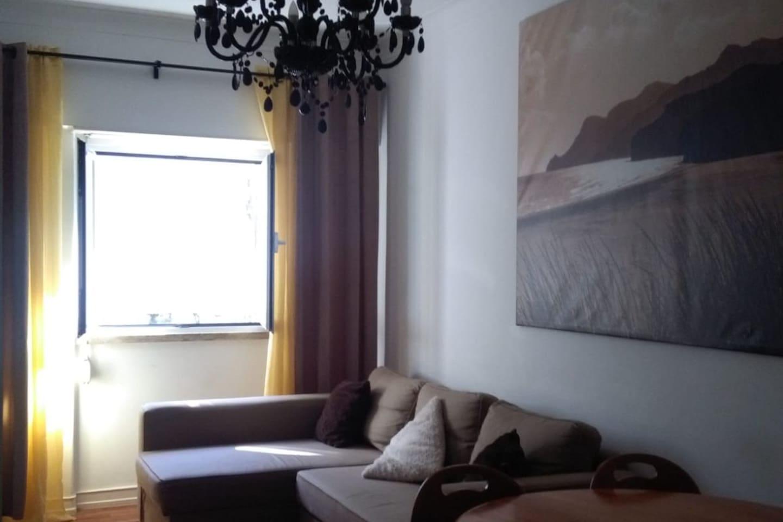 Sala com sofá, TV, mesa de trabalho ou refeições