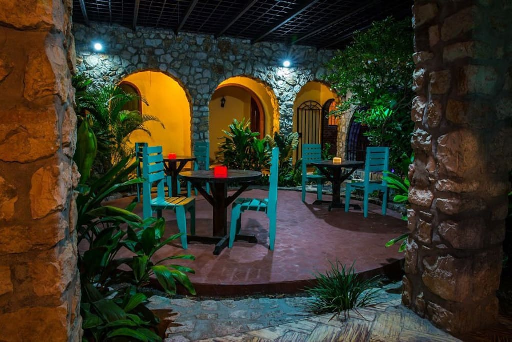 The rooms surround this gorgeous patio with natural stone arches and upcycled pallet furniture made by Haitian carpenters. Color-changing solar lights bring the house to life at night!