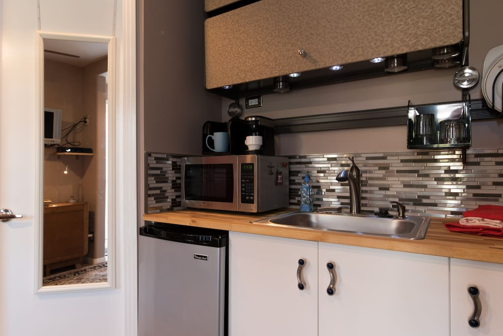 a kitchenette with refridgerator, microwave, coffee and hot water maker, toaster, etc.