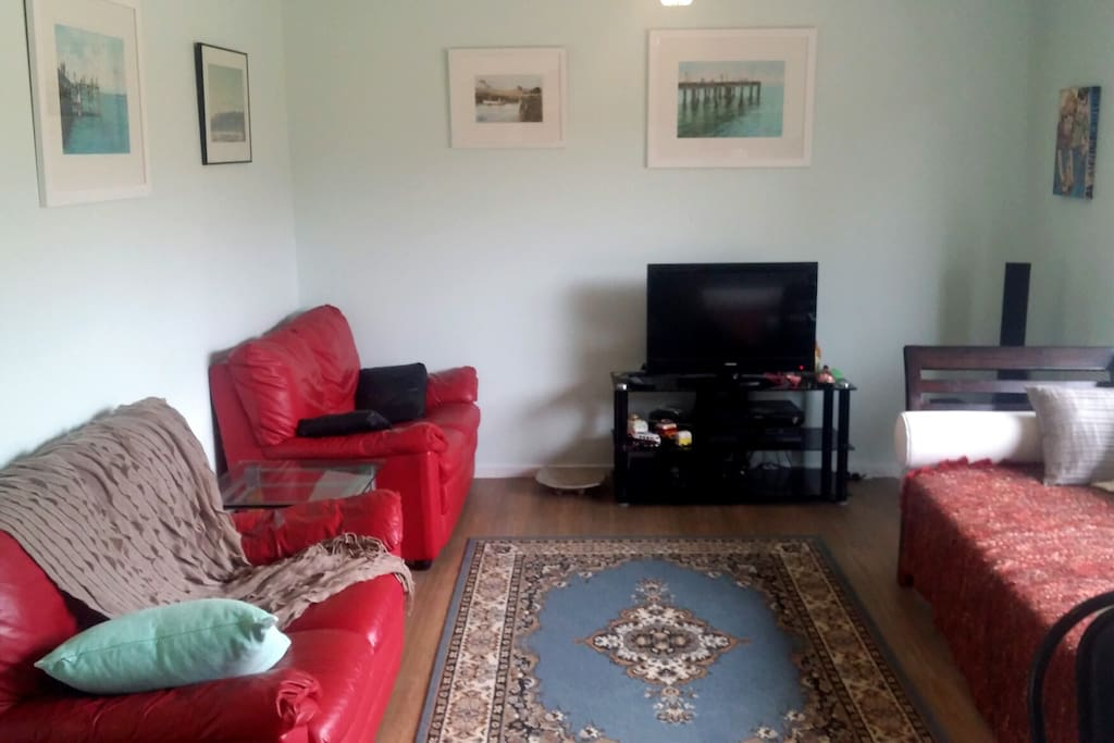 Large comfortable lounge room, plenty of seating, tv, table and chairs, bookcase
