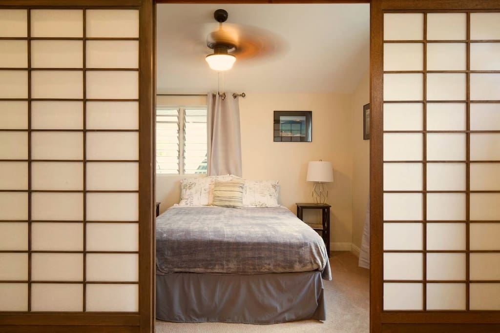 Your bedroom with queen-size bed, ceiling fan, and sliding Japanese shoji doors for privacy.