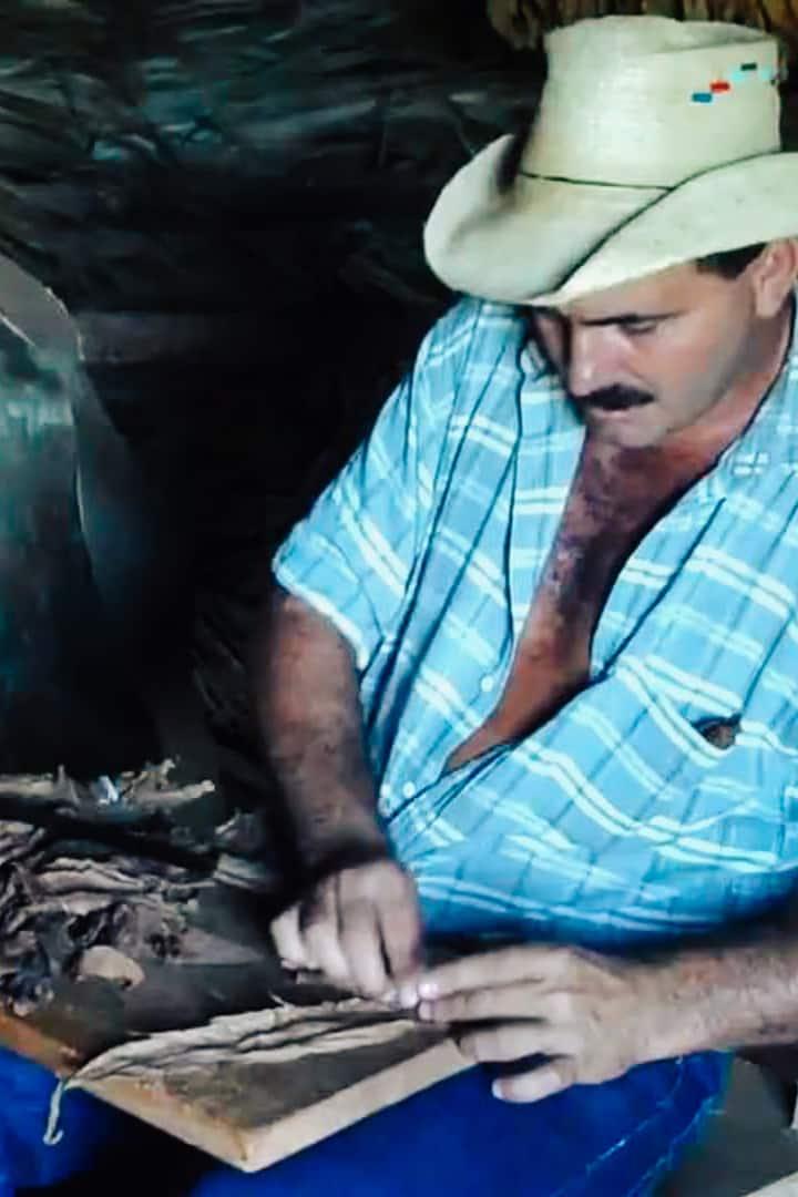 Farmer Benito rolling a cigar.