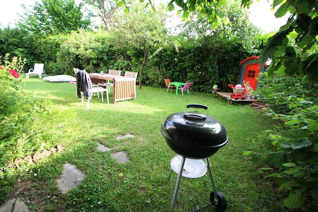 Jardin de 200 m², avec tables, chaises, bains de soleil, coussins et jeux pour enfants.