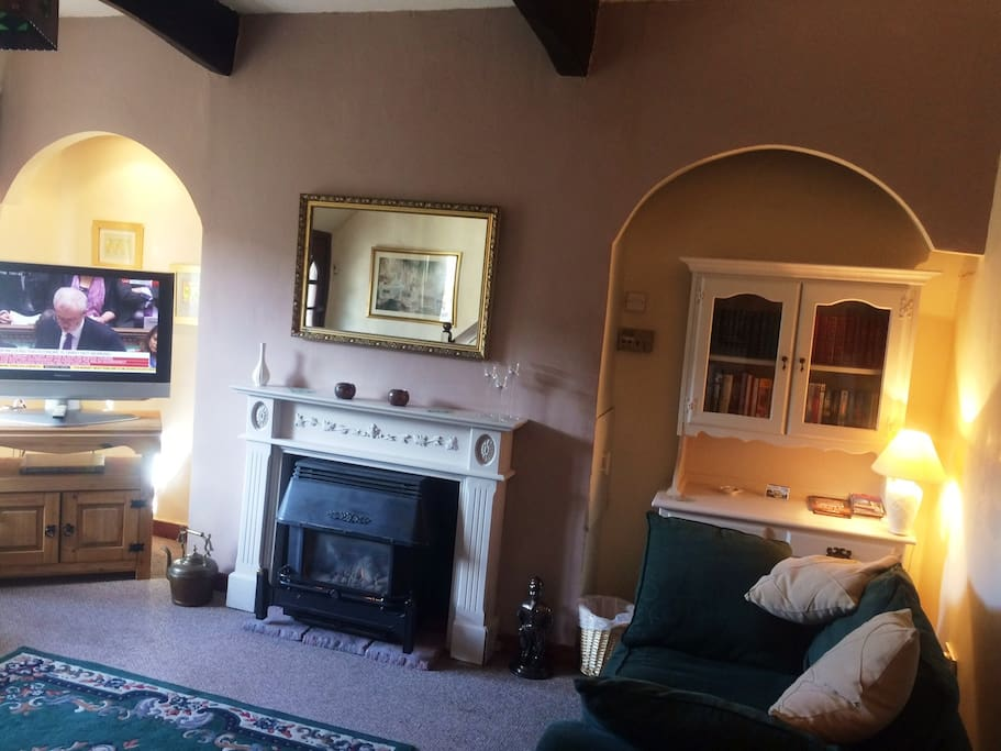 Comfortable lounge with oak beams a living flame burner and period features