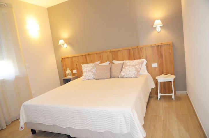 L'accogliente camera matrimoniale con letti king size, testata e panca di legno di cedro.