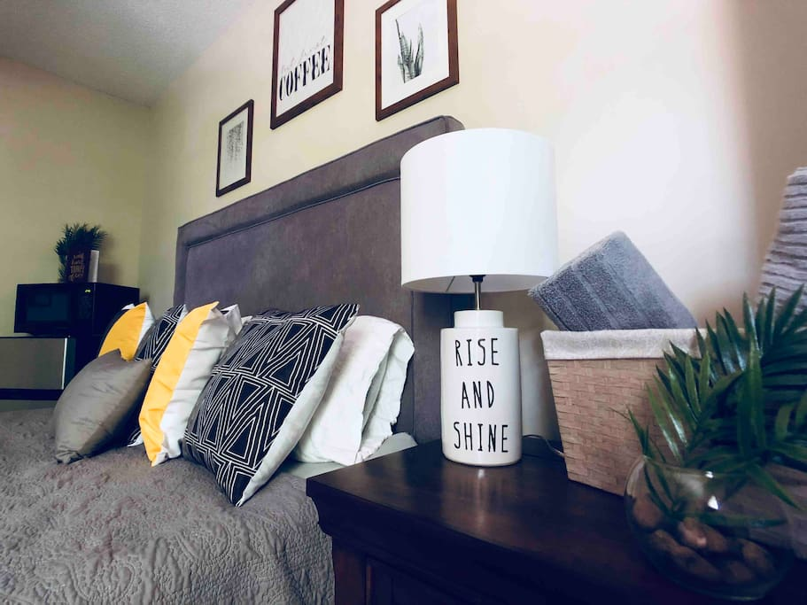 Bedside table has a bright lamp. It also provides storage for a longer stay as well as a built in outlet for any charging needs.