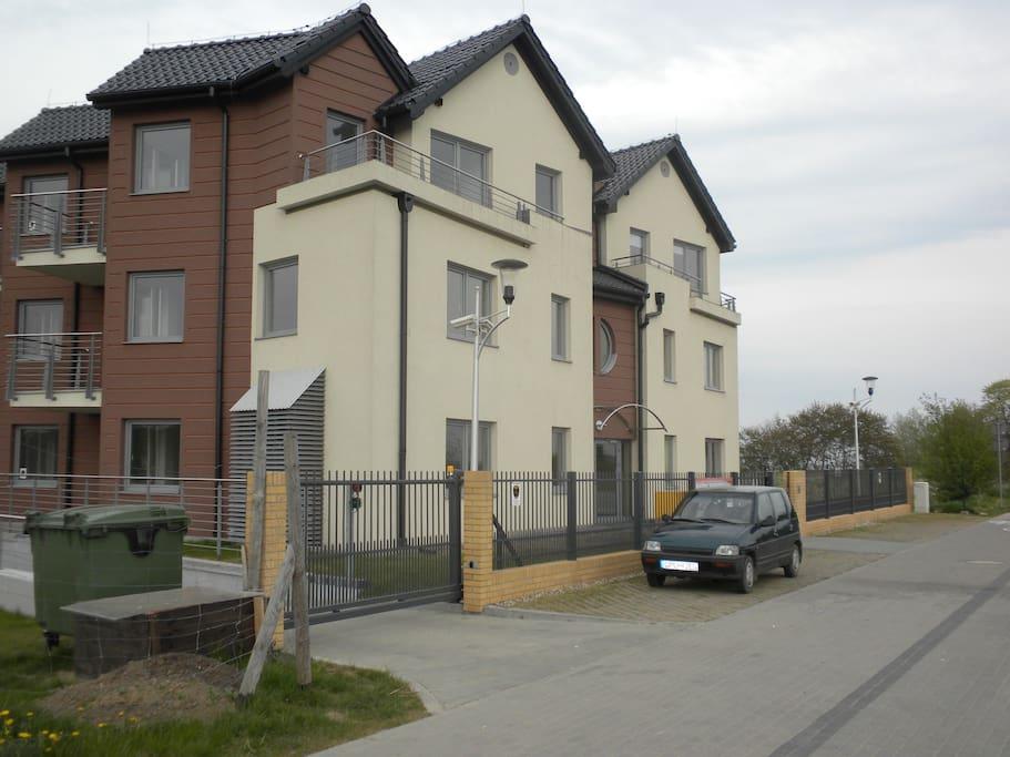 budynek od ulicy z wjazdem do garazu; view from the street with the gate to underground parking