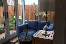 Sitting area, with tea, coffee making facilities  looking out onto and with french windows into courtyard garden.